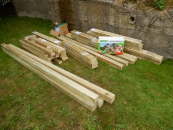 Takto vypadá materiál na stavbu dětského hřiště - nařezané dřevo a krabice s komponenty.